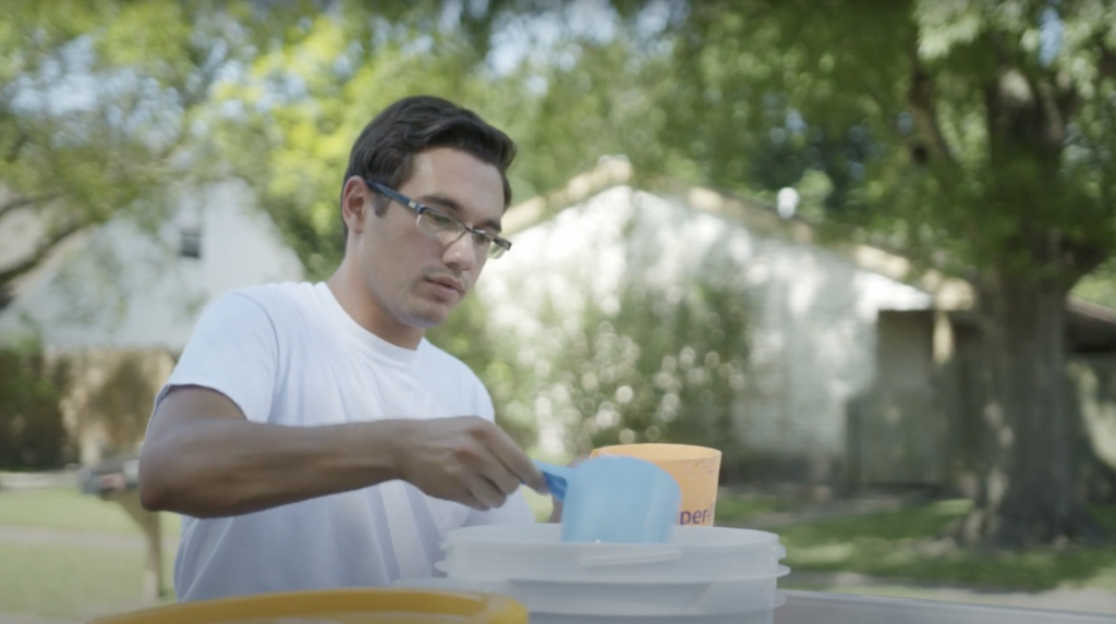 An experienced Clyr Crew member getting pool chemicals from a bucket